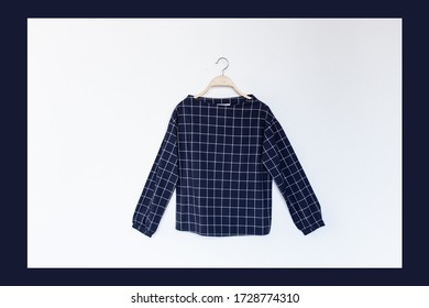 Blue colour blouse is clothes hanger on white background.