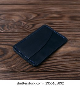 Blue colour handmade leather one pocket cardholder on wooden background. Stock photo with soft blurred background.