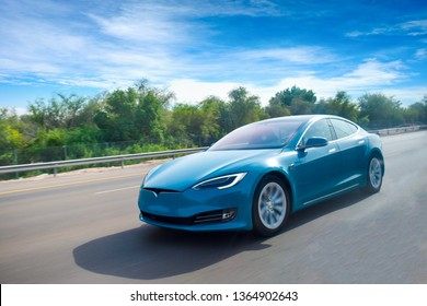 A blue coloured electric car cruising on highway,with clear blue sky.green energy concept.Have space for text.