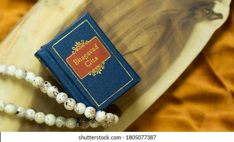 Blue coloured holy Hindu Book Bhagavad Gita nicely kept over a wood and satin gold cloth  - Shutterstock ID 1805077387
