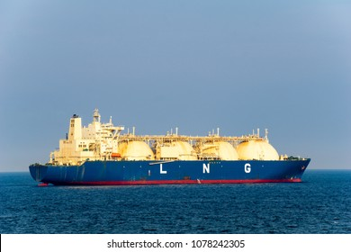 Blue coloured hull large liquefied natural gas (LNG) carrier with 4 LNG tanks sails along the sea.