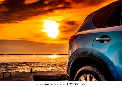 Blue compact SUV car with sport and modern design parked on concrete road by the sea at sunset. Environmentally friendly technology. Business success concept. Blue SUV car door with handle