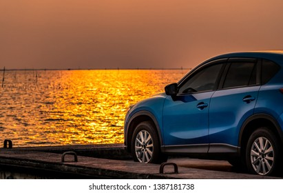 Blue compact SUV car with sport and modern design parked on concrete road by the sea at sunset. Environmentally friendly technology. Electric car technology and business. Hybrid auto and automotive.
