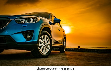 Blue compact SUV car with sport and modern design parked on concrete road by the sea at sunset. Environmentally friendly technology. Business success concept.