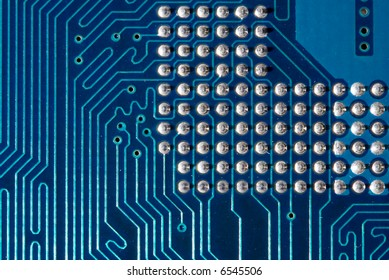 Blue computer motherboard with processor pins. Extremely close-up