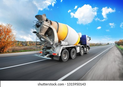 Blue concrete mixer truck driving fast on the countryside road with trees against blue sky with clouds