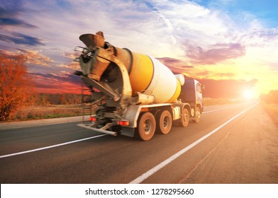 Blue concrete mixer truck on the countryside road with trees against night sky with sunset