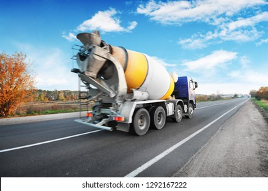 Blue concrete mixer truck on the countryside road with trees against blue sky with clouds