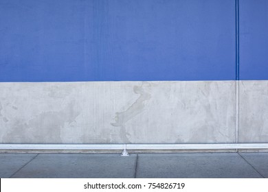 blue and concrete wall background with sidewalk