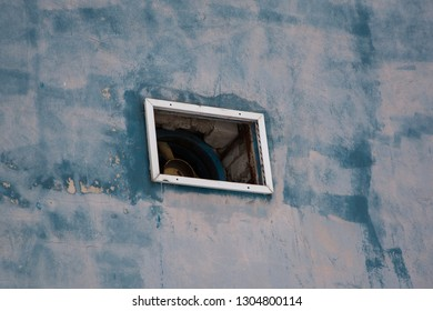Blue concrete wall background, texture. Window and fan in the wall.