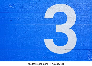 Blue concrete wall with stencil number 3