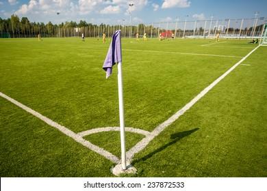 Blue corner flag on soccer field at sunny day