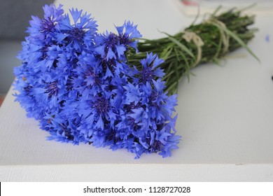 Blue cornflower bouquet on the white wooden table. Beautiful summer flowers