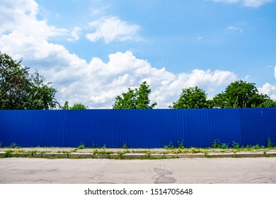 Blue corrugated iron fence against blue sky with clouds