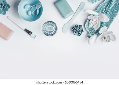 Blue Cosmetic setting for facial skin care with white orchid flowers, homemade mask tools and accessories on white background, top view, place for text. Beauty and nature herbal cosmetic concept