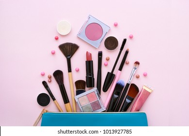 A blue cosmetics bag with makeup products spilling out on to a pastel pink background. Top view