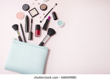 A blue cosmetics bag with makeup products spilling out on to a pastel pink background, with empty space at side