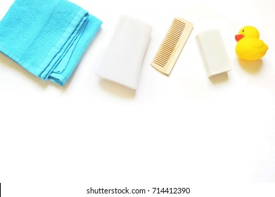 Blue cotton towel, shampoo or shower gel bottle, wooden comb, baby soap and yellow rubber toy duck on a white background. Flat lay stock photography, top view. Beauty products border. Mockup