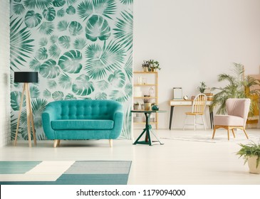 Blue couch between lamp and table in open space interior with green wallpaper and chair. Real photo