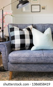 blue couch with black and white gingham plaid pillow board and batten walls and black floor lamp