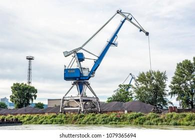 Blue crane in cargo port translating coal. Industrial scene.