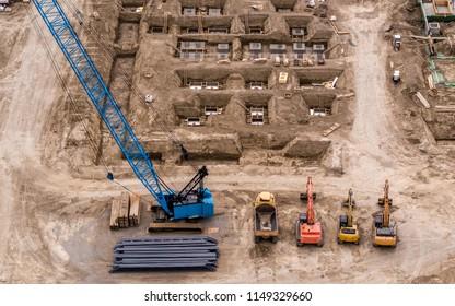 Blue Crane, Orange Excavators on Construction Site, Building Foundation