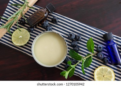 blue and cream striped towel with bluberries, mint, rosemary, lime,  lemon, balm, and little glass viles with a dark stained wood background