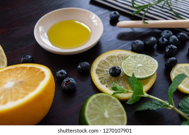 blue and cream striped towel with bluberries, mint, rosemary, lime,  lemon, balm, olive oil, and little glass viles with a dark stained wood background
