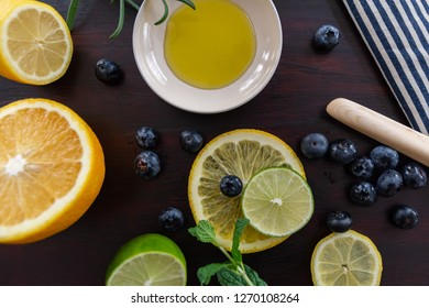 blue and cream striped towel with bluberries, mint, rosemary, lime,  lemon, and orange with a dark stained wood background