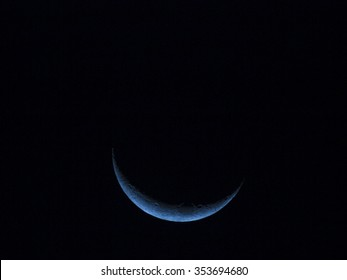 A blue crescent moon in a black night sky, Thailand