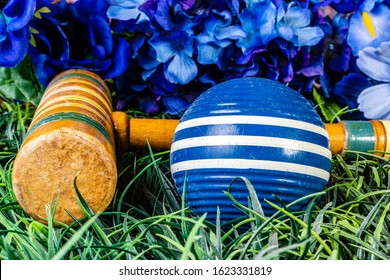 blue croquet ball and wooden mallet with blue flowers