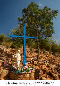 Blue Cross on aparition hill in Medjugorje, with rocky background and green tree, and statue of Virgin Mary