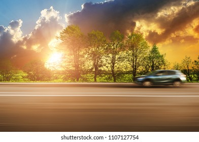 A blue crossover car driving fast on the countryside asphalt road in motion with green trees against night sky with sunset