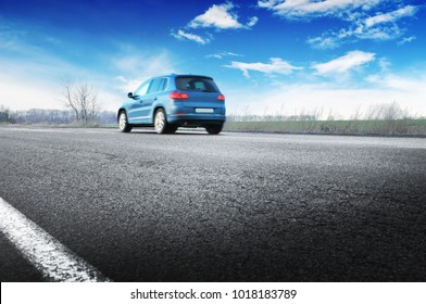 A blue crossover car on the countryside asphalt road against blue sky with white clouds