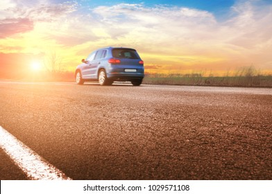 A blue crossover car on the countryside asphalt road against night sky with sunset