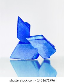 Blue crystals of copper sulfate on mirror surface, white background, selective focus