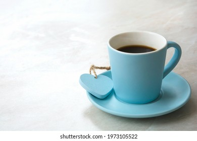 blue cup with black coffee and heart on light blurred table background with empty space for text