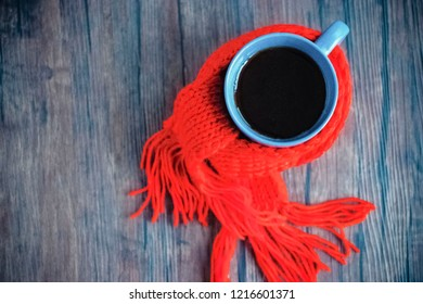 Blue cup with black tea, coffee or hot chocolate in  red scarf on brown wooden background. The concept of home comfort in cold season. Hugge.