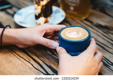 A blue cup of coffee in hands on wood table with dessert and drink