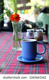 Blue cup of coffee on quilt table cloth with vase of orangy red spring flower on the background