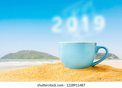 blue cup of coffee on white sand beach over blue sky and sea on day noon light background.