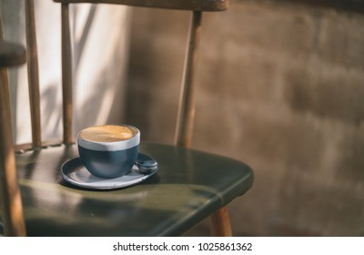 the blue cup of coffee on wood table in vintage color mood