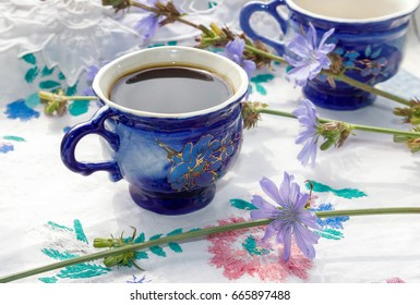 Blue cup of coffee tea chicory drink with chicory flower,  hot beverage on embroidered fabric background