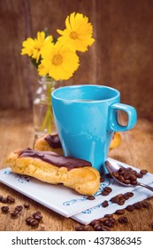 blue cup with fresh coffee and yellow flowers in glass container