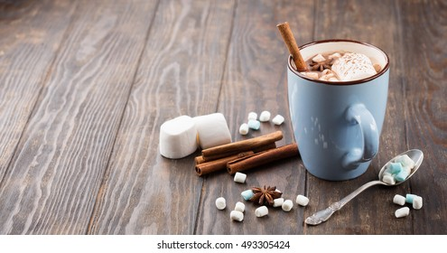 Blue Cup of hot Chocolate drink with Marshmallows and cinnamon on dark wooden background. Winter time. Holiday concept, Selective focus