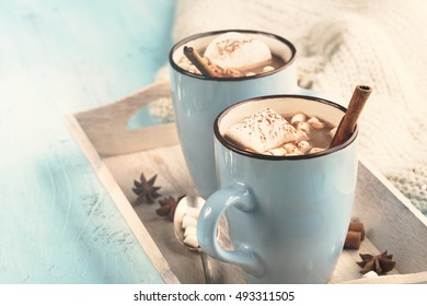 Blue Cup of hot Chocolate drink with Marshmallows and cinnamon on blue wooden background. Winter time. Holiday concept, Selective focus, toned