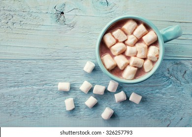 Blue cup of hot cocoa with marshmallows on blue wooden background