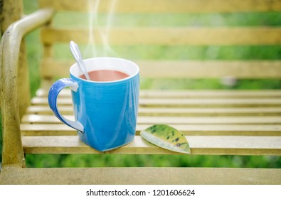 Blue cup of hot coffee with nuture background.