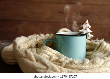 A blue cup with hot tea and a white knitted scarf on a dark wooden background.