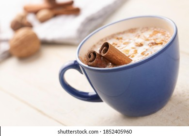 Blue cup of salep milky hot drink of Turkey with cinnamon powder and sticks healthy spice and autumn winter içeceği on white rustic vintage wooden table.